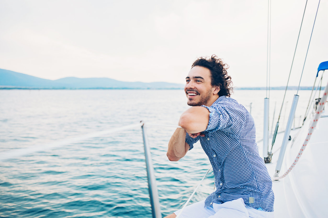 Man smiling on sailboat | Annapolis Orthodontics Annapolis, MD