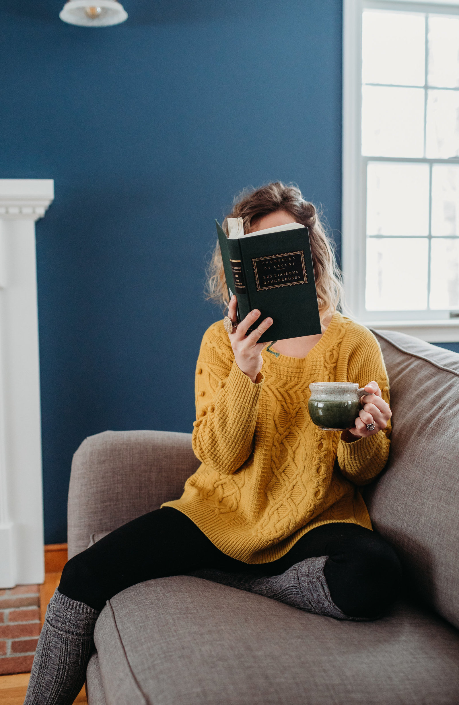 woman sits on a couch in a blue room with book and coffee mug