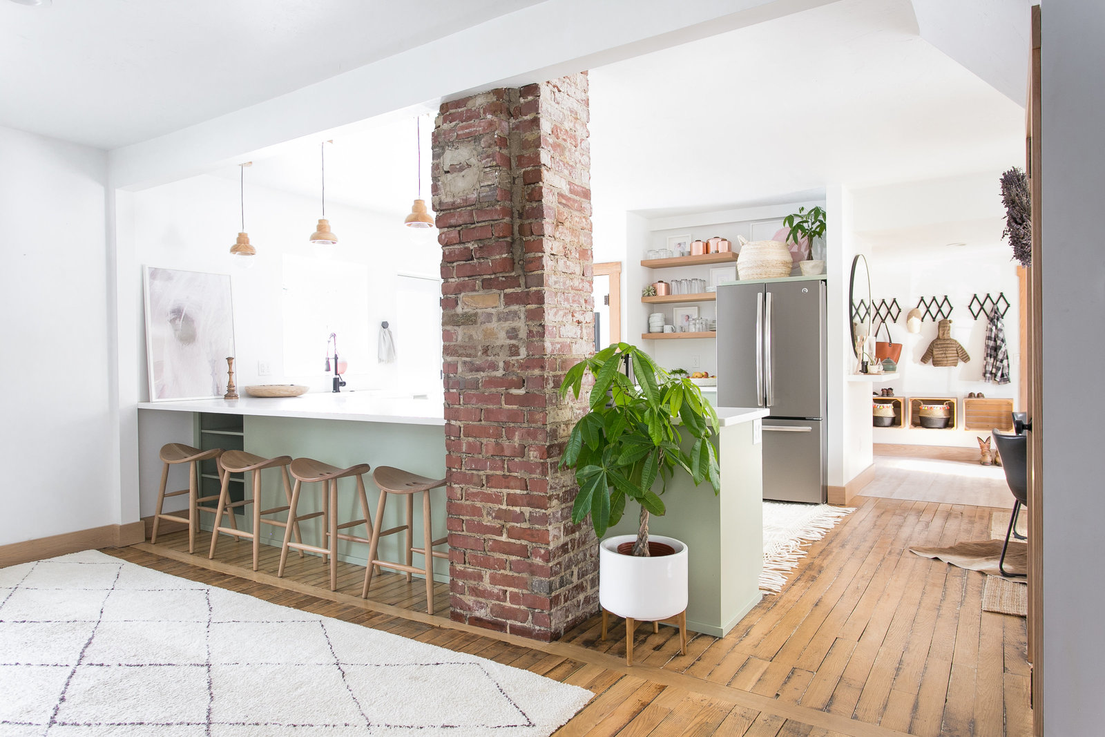 Modern farmhouse design with open concept. Design includes exposed brick, refurbished flooring, floating shelves, sage cabinetry and simple wood pendants