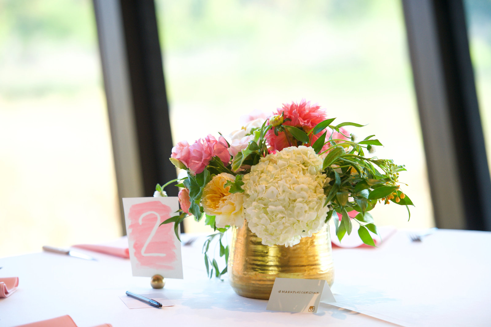 lush and low wedding centerpiece with watercolor table number