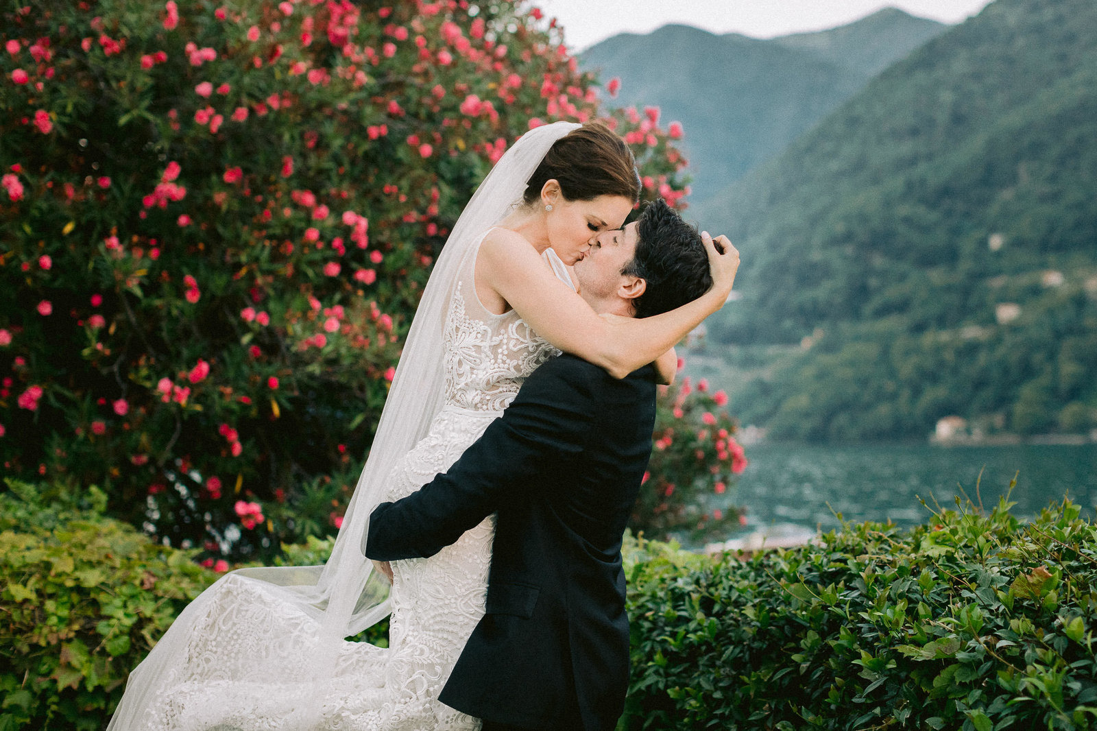 bride kissing groom in front of pink flowers