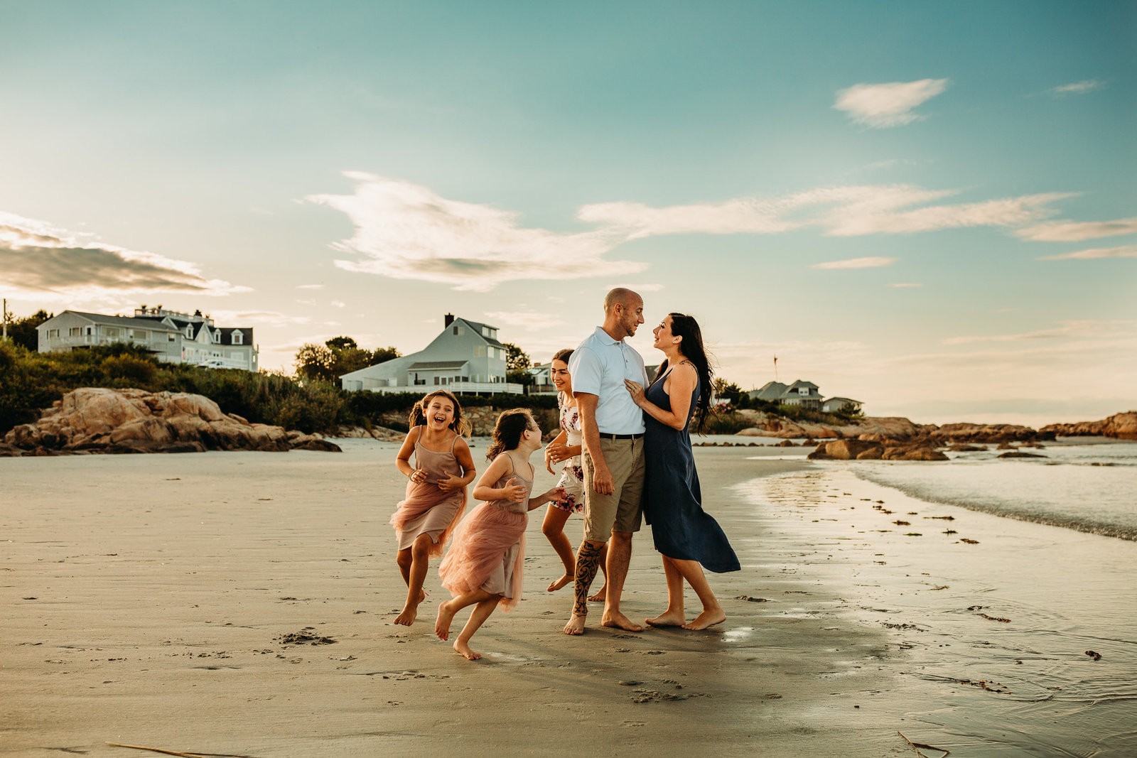 couple stands together on beach while daughters run around in family photo session