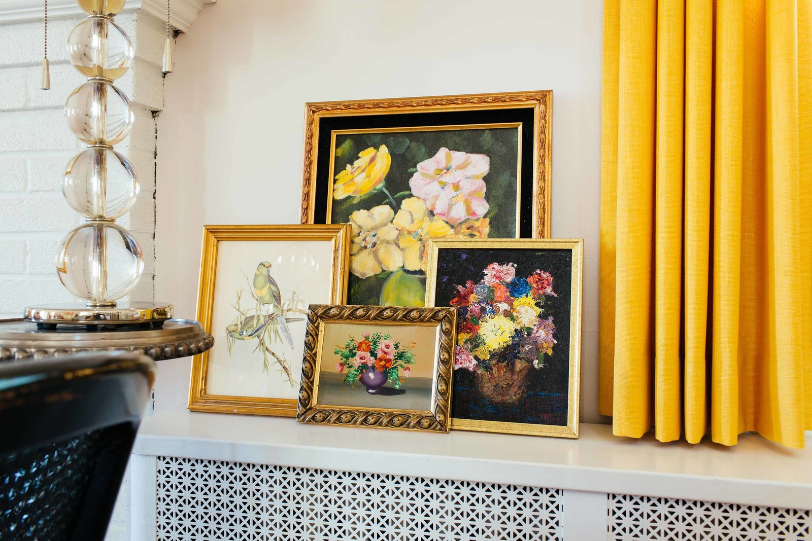 Four framed art prints on a shelf beside a yellow drape.