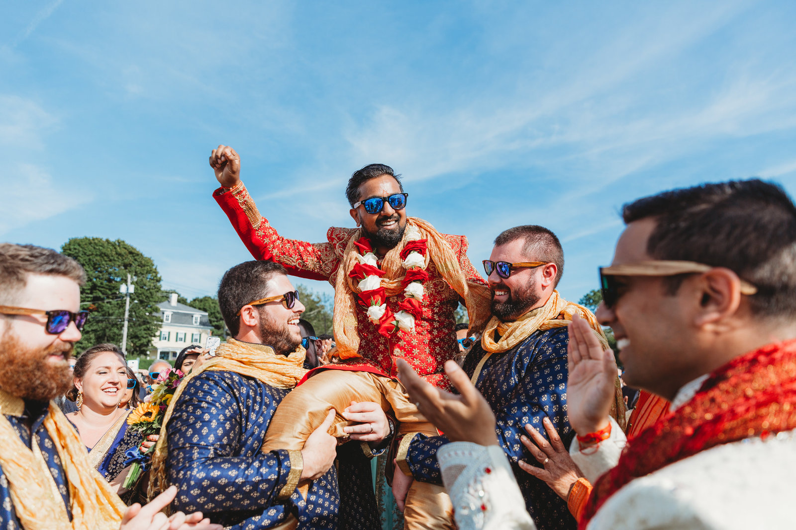 groomsmen lift indian groom into air during parage before ceremony