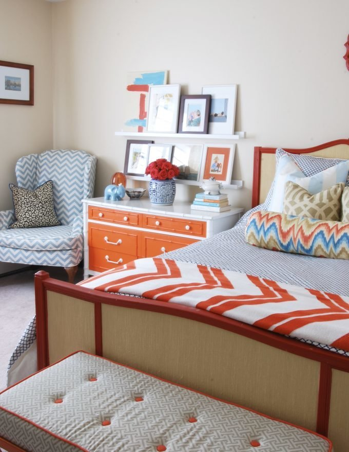 A colorful bedroom with a bed, dresser, chair, and accessories.