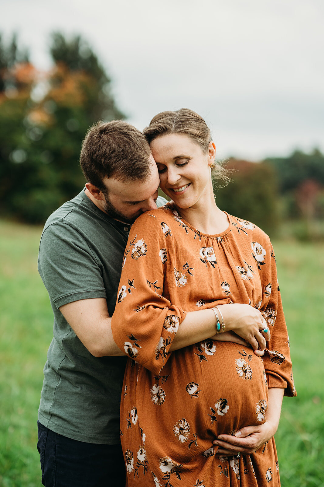 pregnant couple snuggles during autumn pregnancy pictures