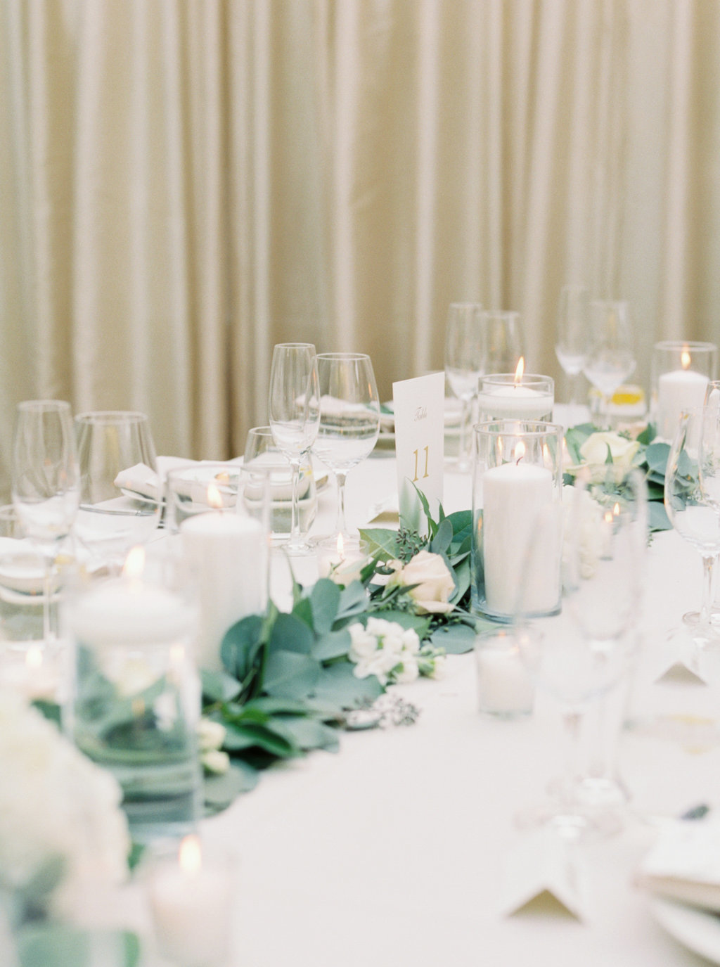 wedding reception table setting with eucalyptus garland and white floral centerpieces at Butterfly Lane Estate