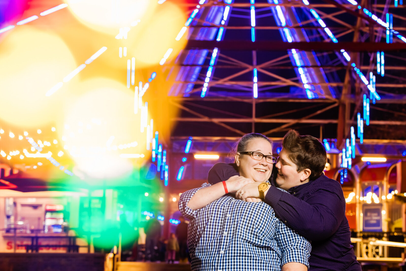 Colorful engagement photo of an LGBT couple at the St. Louis Wheel in downtown St. Louis