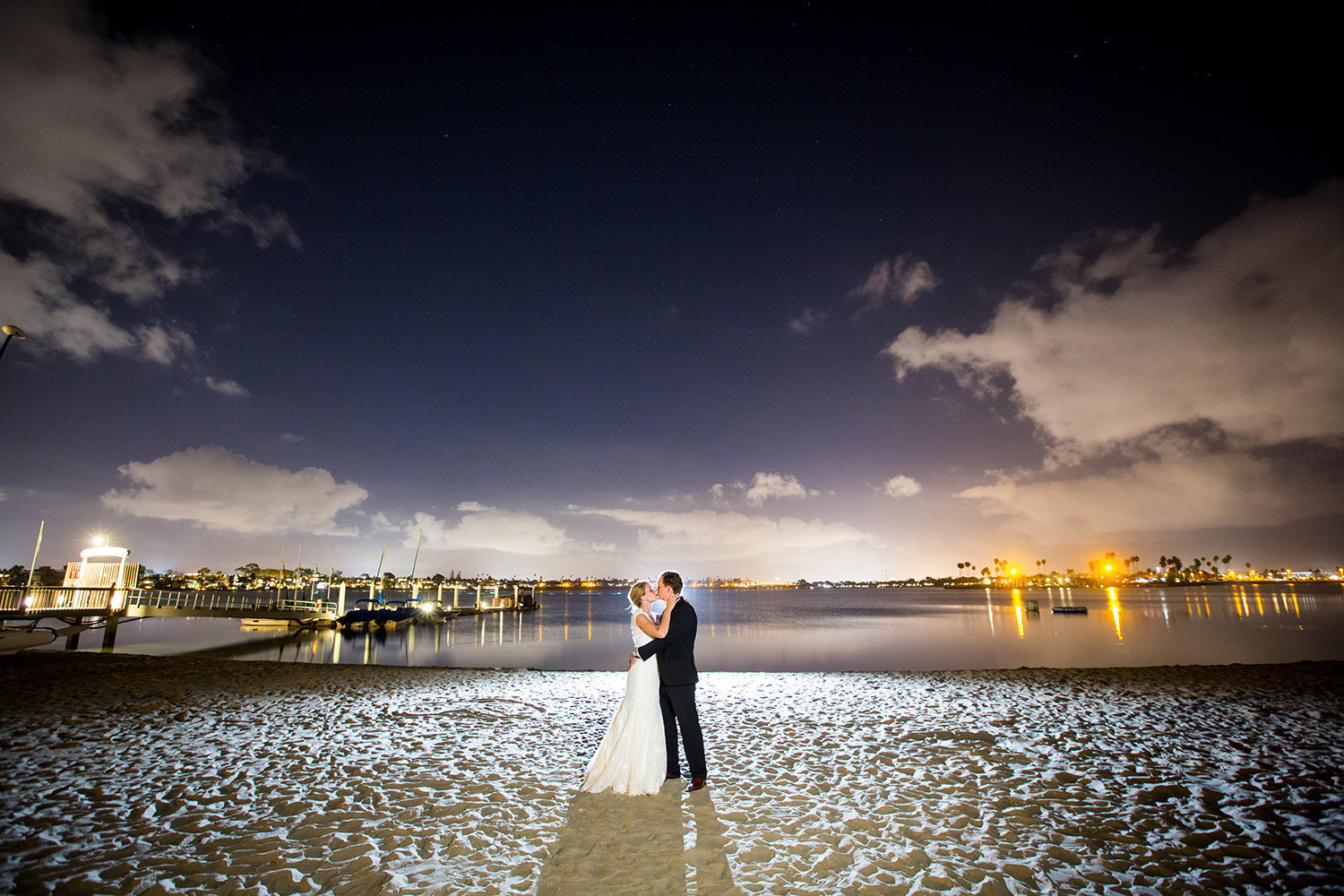 night image of bride and groom and bay in background