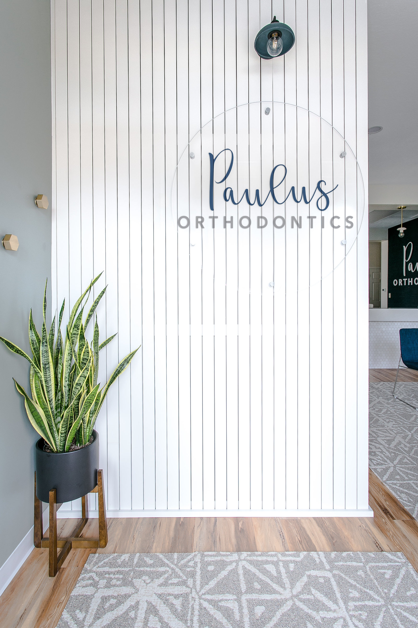 Modern Boutique style Orthodontist office with acrylic sign and vertical shiplap design