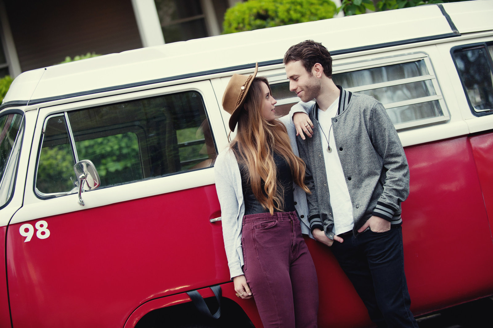 a hipster couple stand in front of a vw van in portland