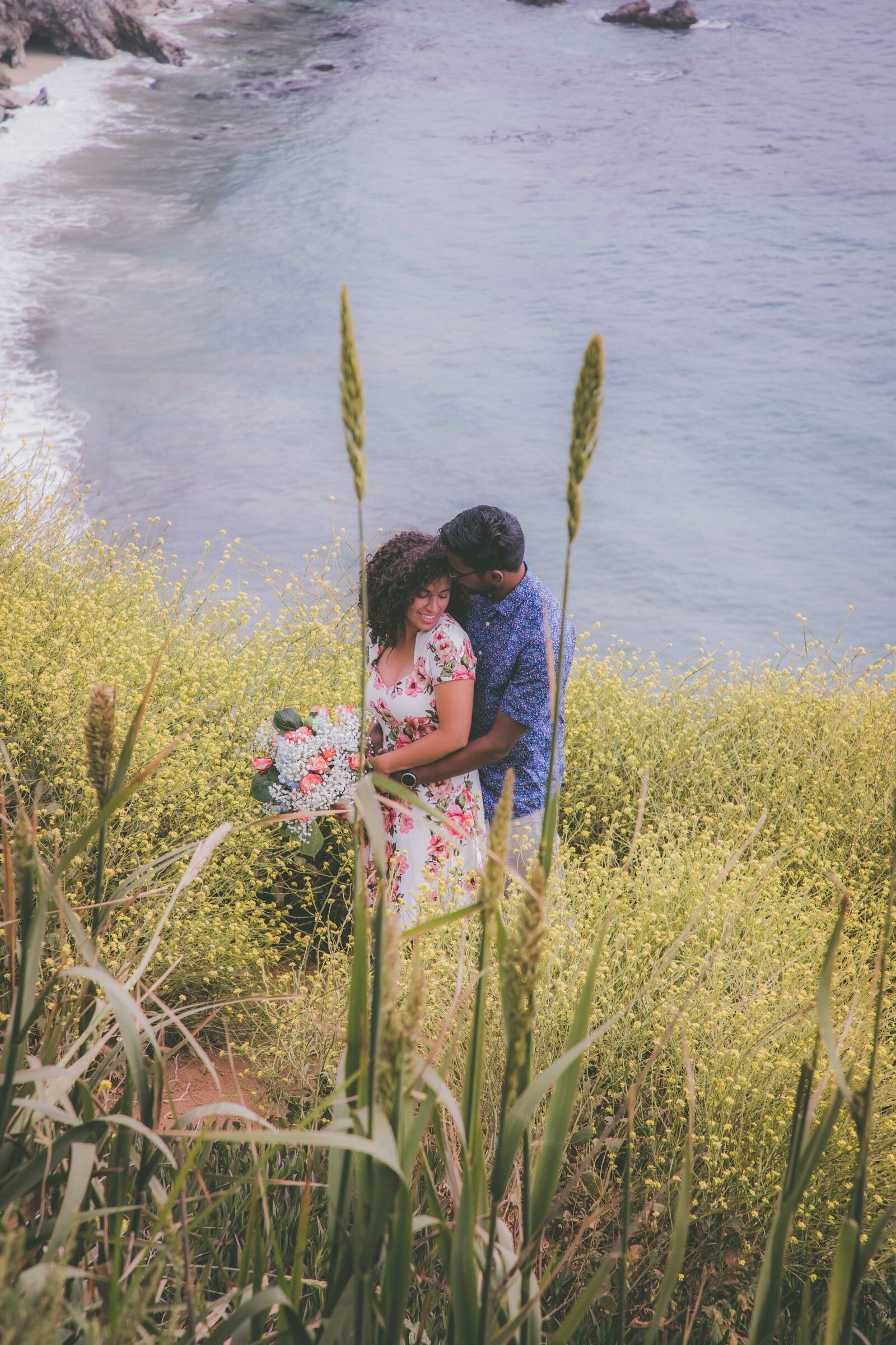 Couple is framed in cattails among yellow wildflowers in Big Sur.