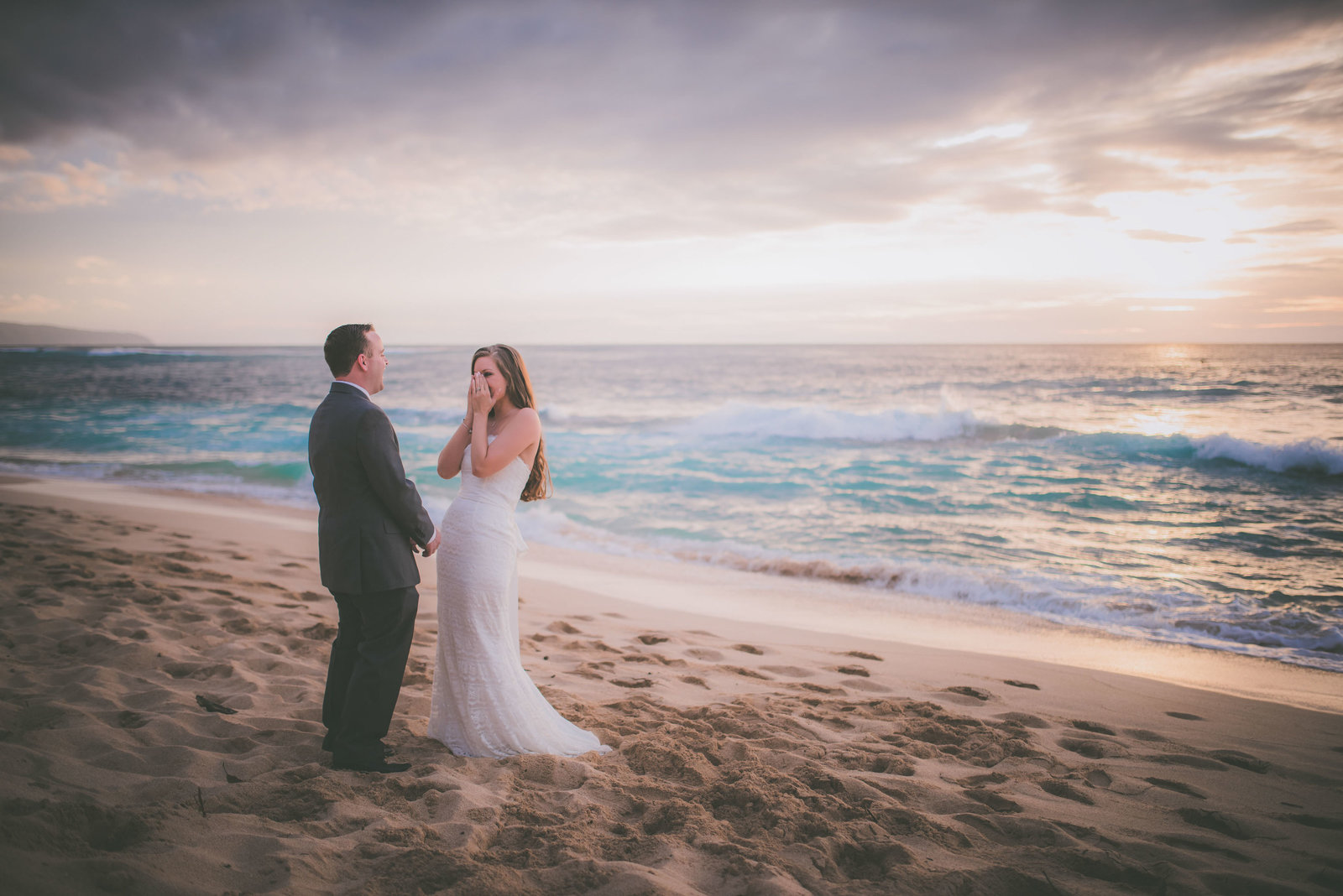 Bride places hands on her face while looking at groom on Oahu beach.