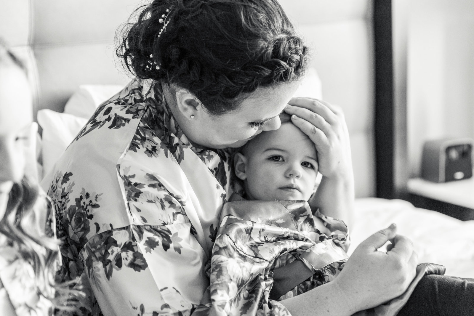bride in floral robe holds toddler daughter on wedding day