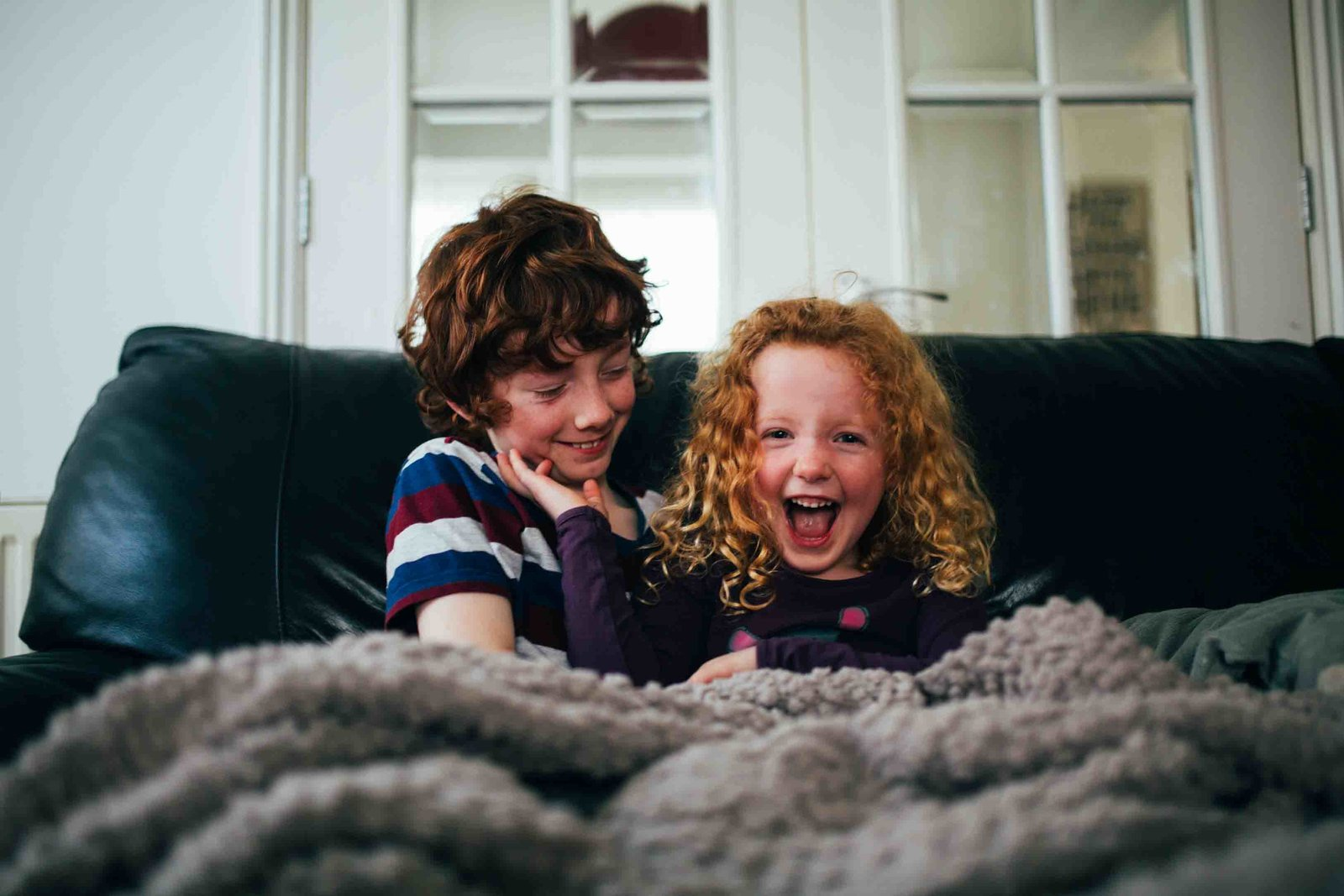 Photograph of ginger brother and sister tickling each other on the sofa at home in Ipswich, Suffolk