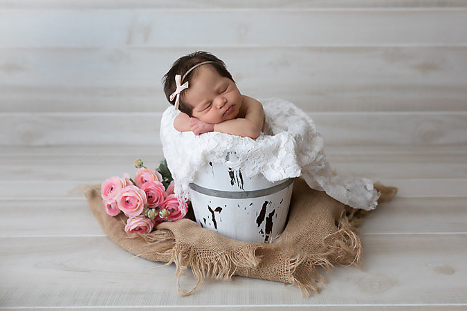 newborn baby girl in white shabby chic bucket with pink flowers