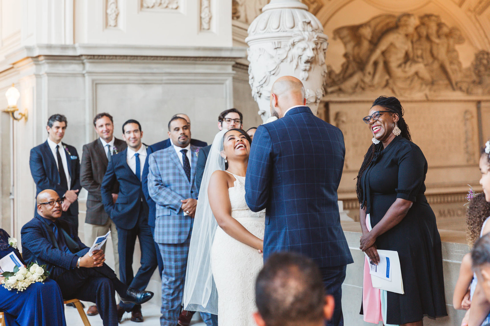 large 4th floor wedding held at san francisco city hall as bride laughs