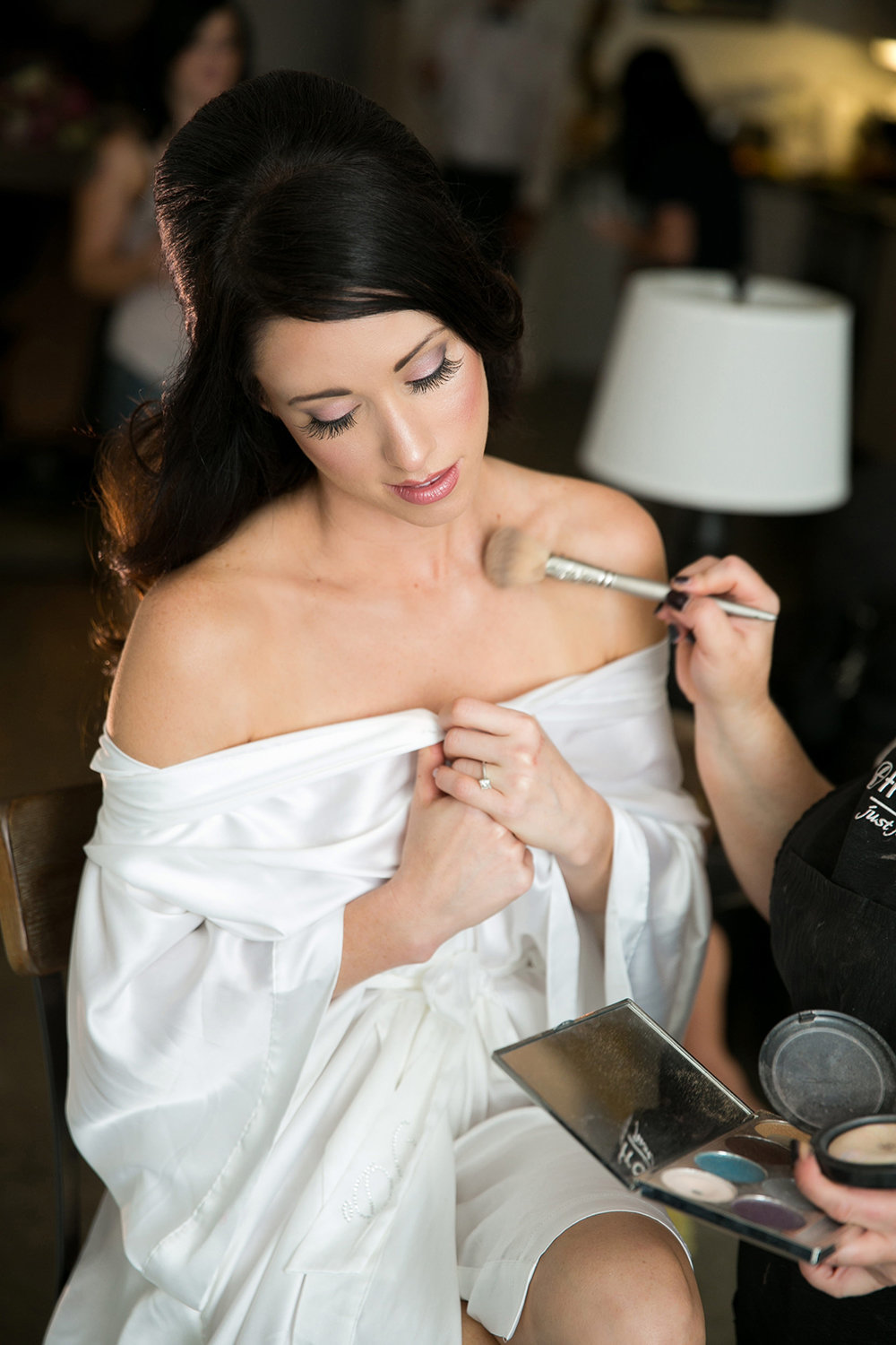 A bride having her makeup done before her wedding