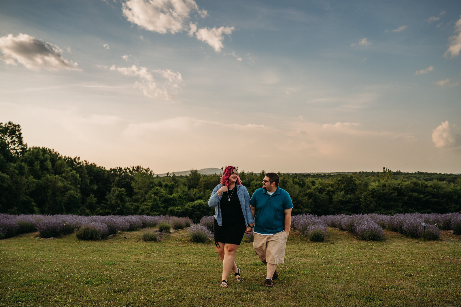 couple walks hand in hand in lavender farm in massachusetts