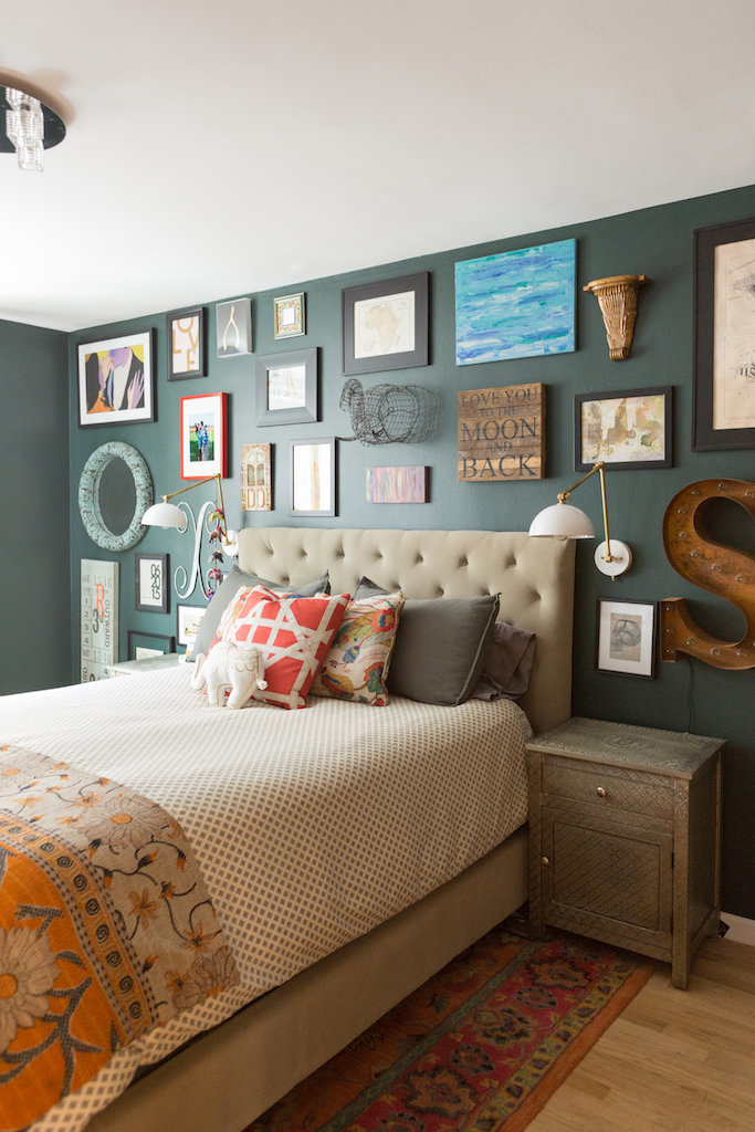 A bed with a tufted headboard and gallery wall.