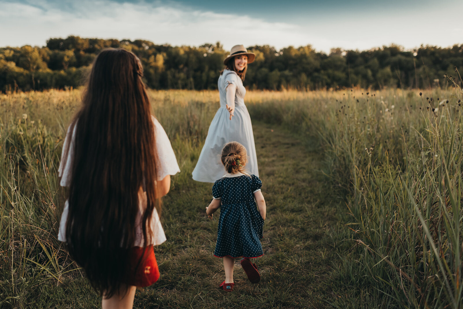 mom reaching for daughter's hand in field