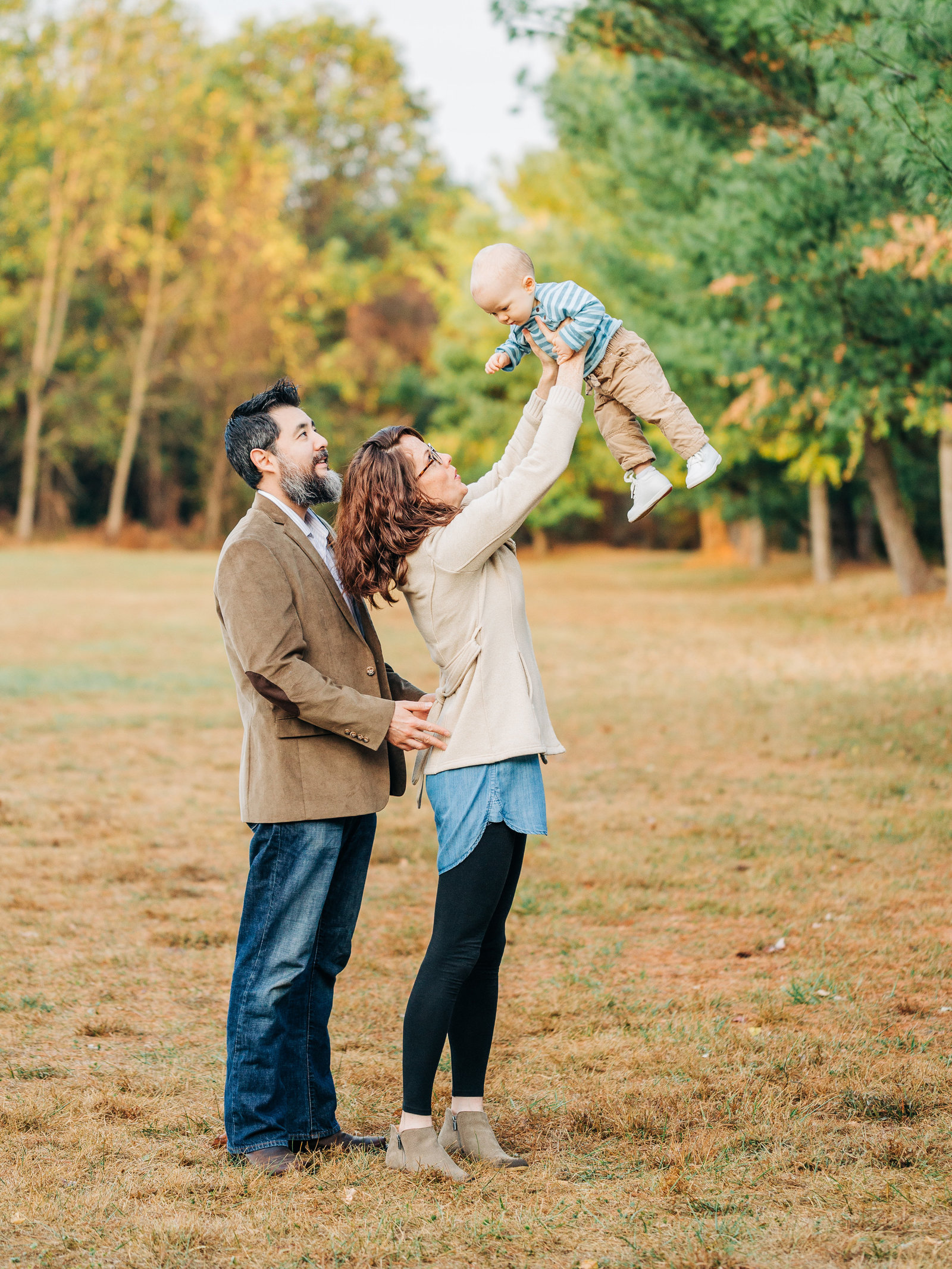 Mother lifts up her baby in the air with fall trees in the background while her husband holds her close