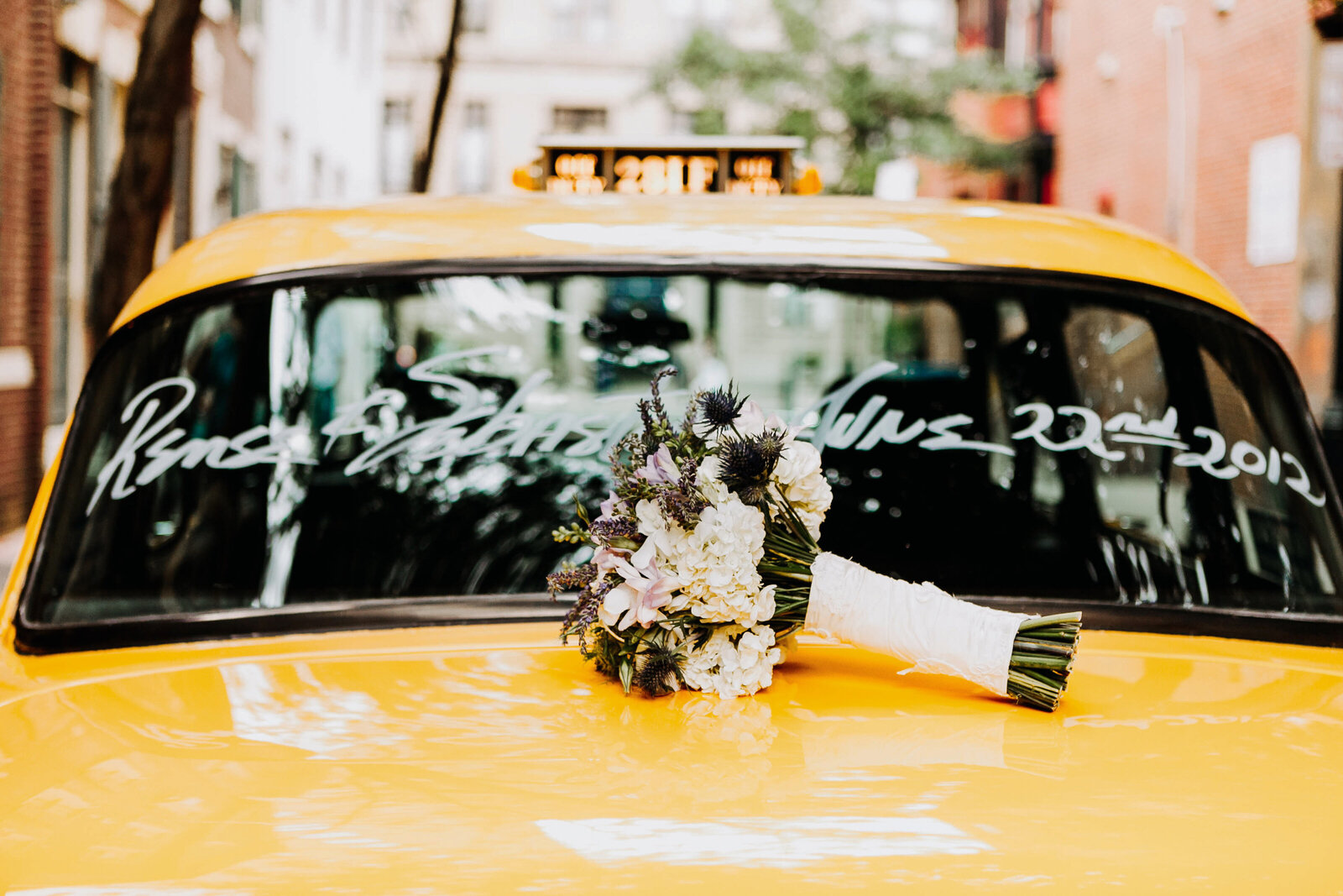 bridal bouquet on yellow taxi cab