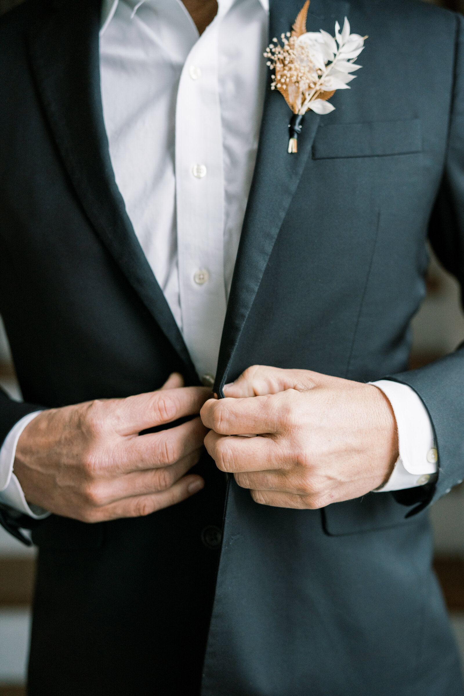 groom buttoning up his black suit