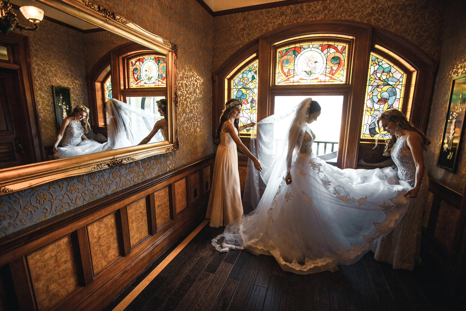maid of honor and mother of the bride do final touches by the stained glass window at the newhall mansion