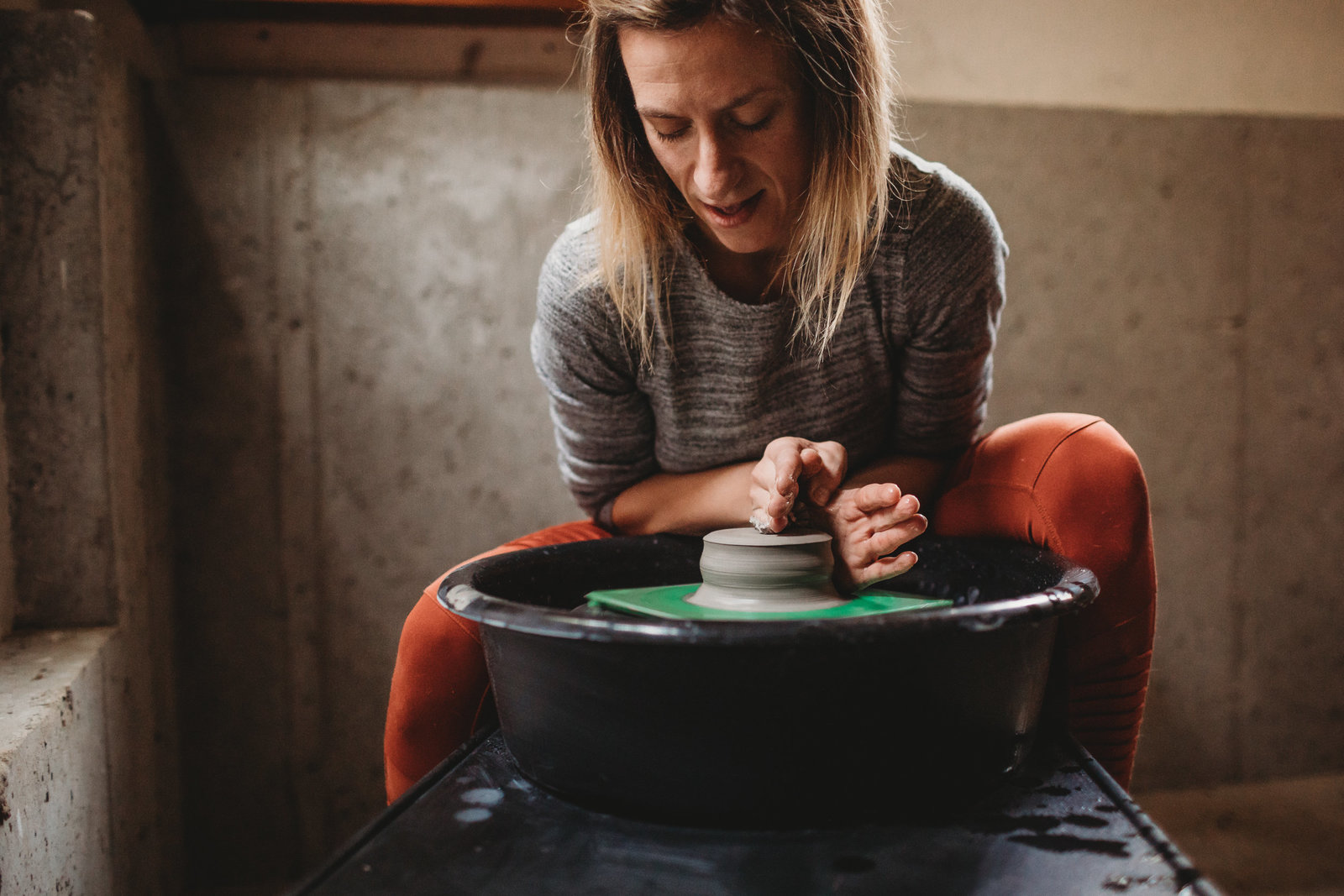 woman shapes clay on wheel in basement workshop