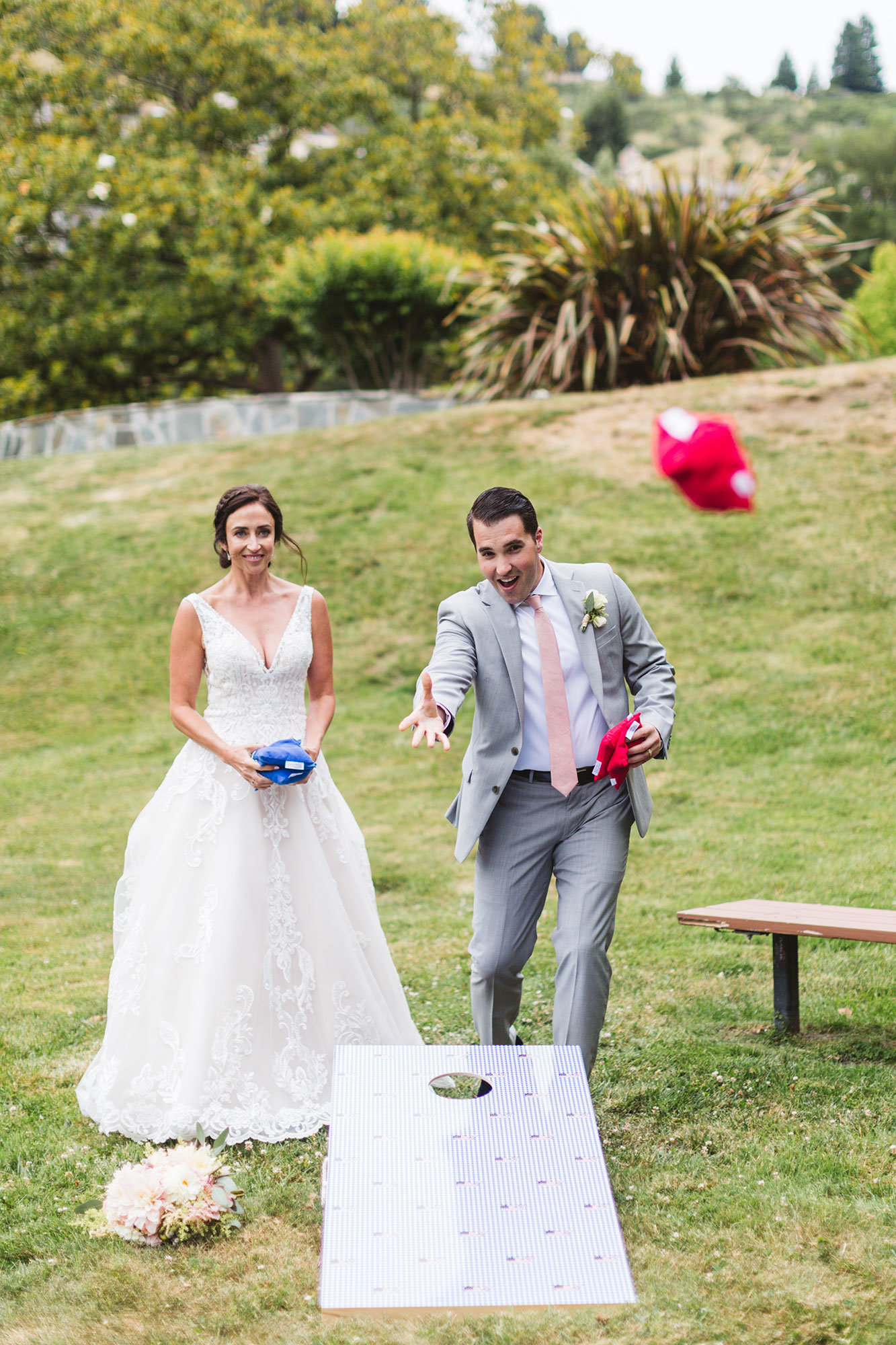 bride and groom playing cornhole at highlands country club east bay wedding
