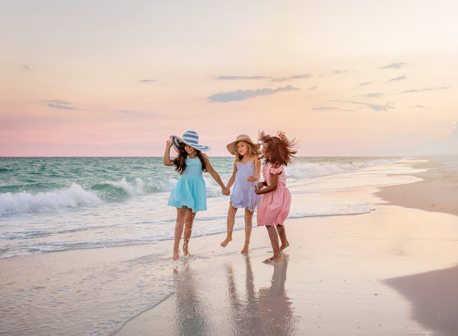 three girls in colorful dresses dancing on navarre beach