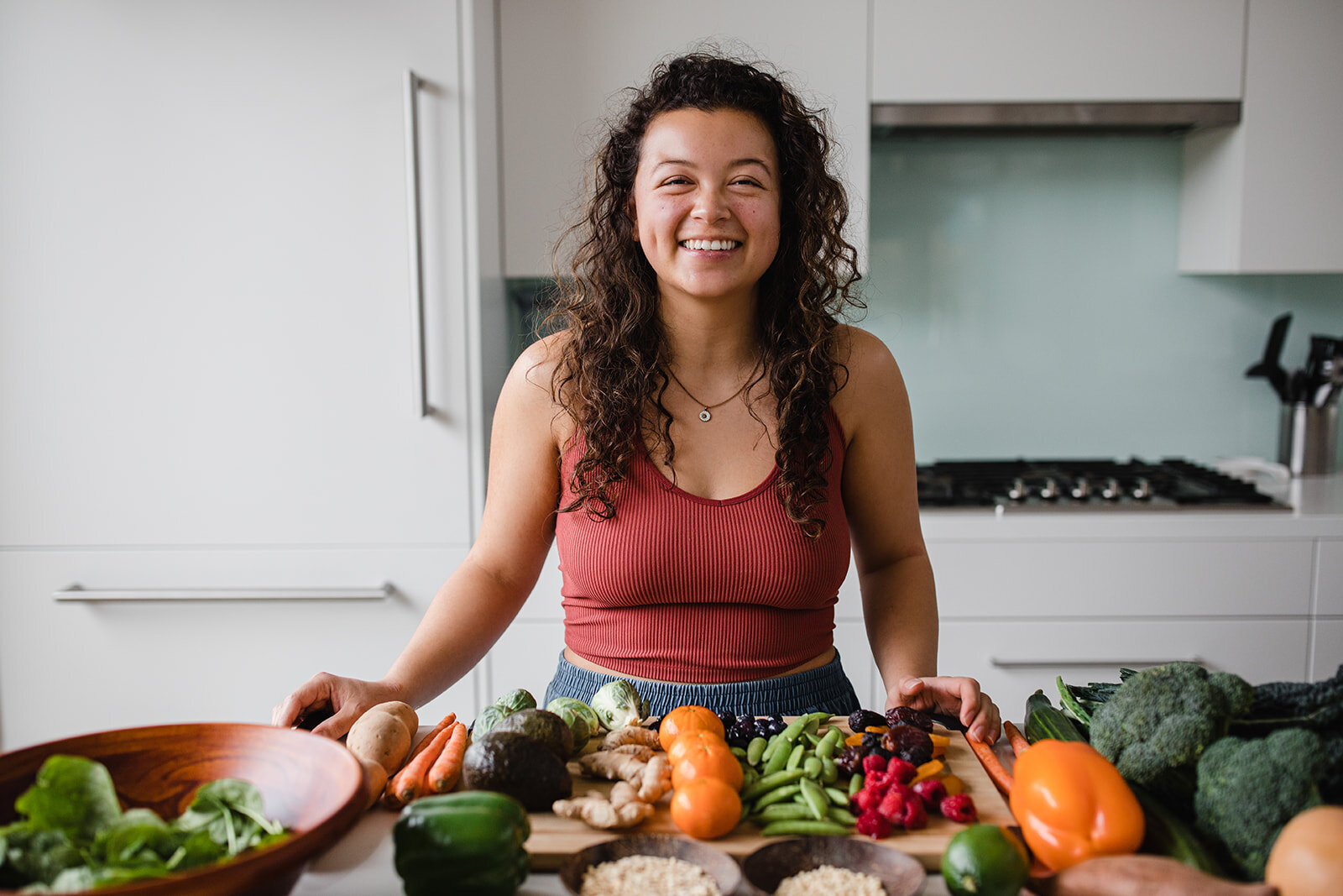 Woman smiling in kitchen with fresh vegetables