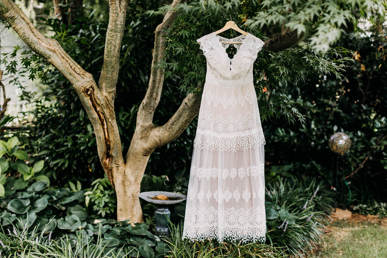 lace wedding dress hanging in tree