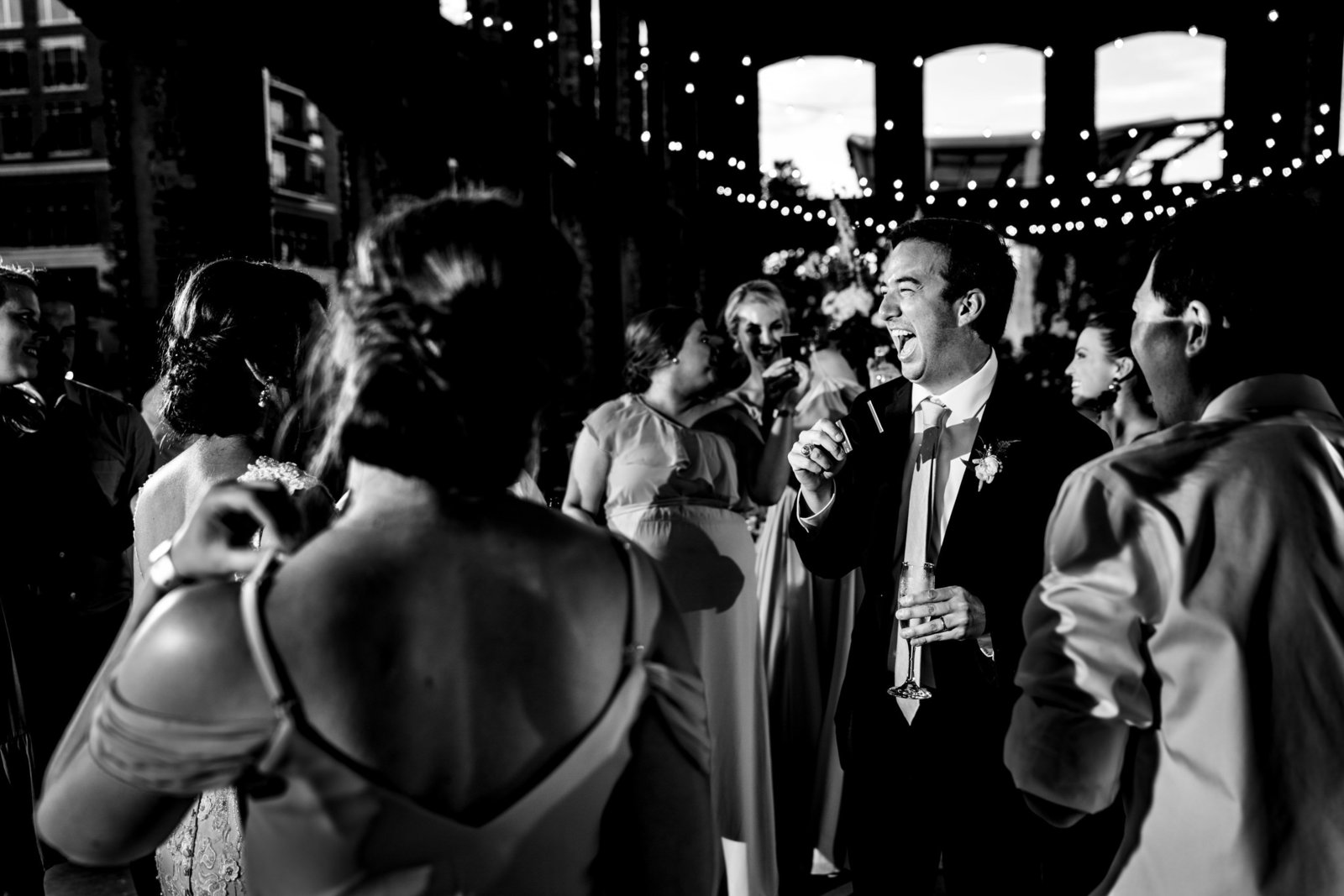 groom dancing under lights