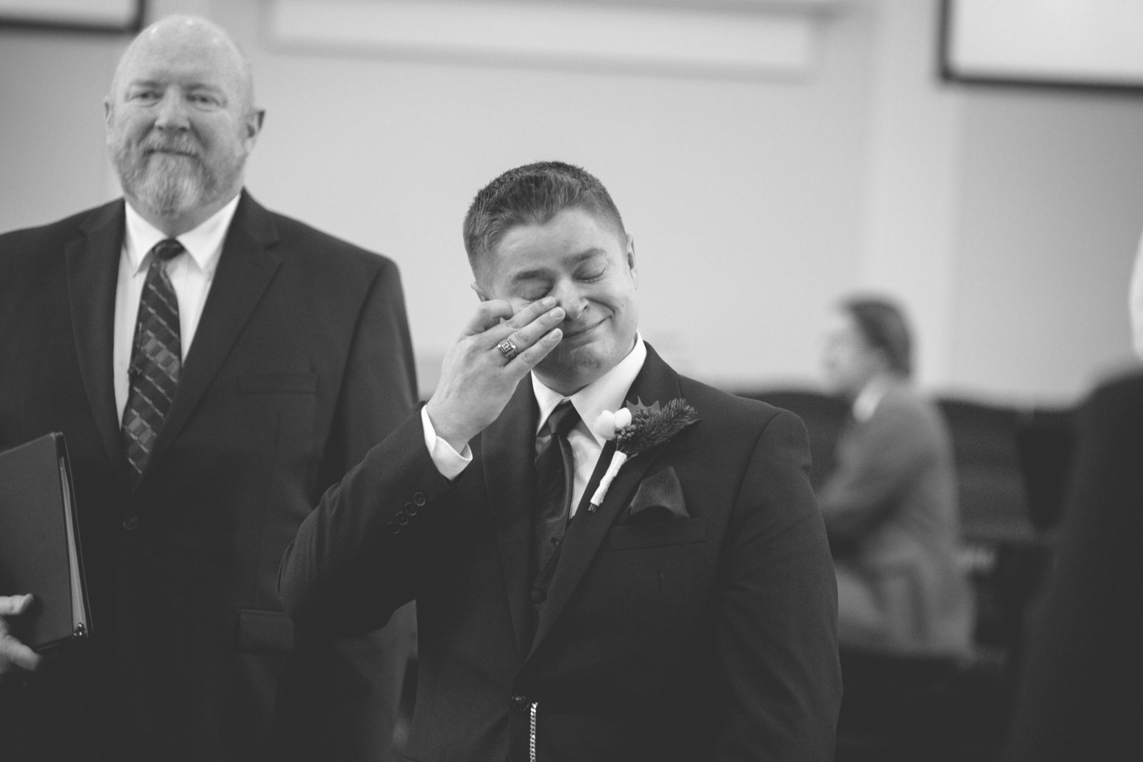 groom wipes a tear from his eye as his bride comes down the aisle of a church in pittsburgh