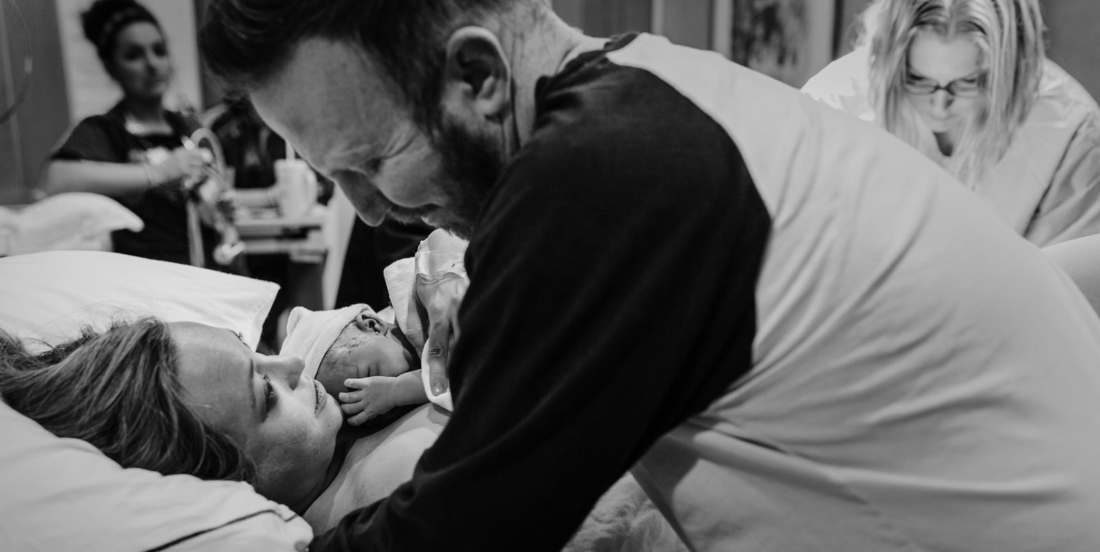 charlotte birth photographer jamie lucido captures a beautiful image as newborn is placed on mother and father embraces them both as midwife delivers the placenta