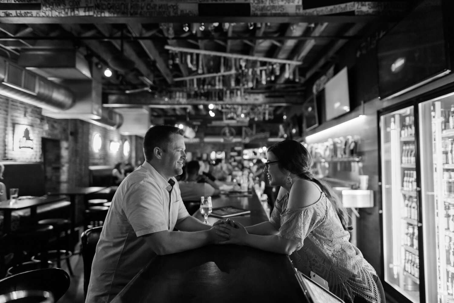 Engaged couple holding hands across a bar in St. Louis