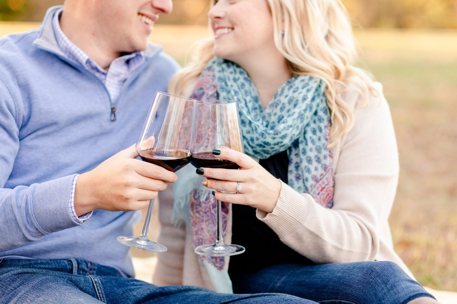 Engaged couple sharing glass of wine
