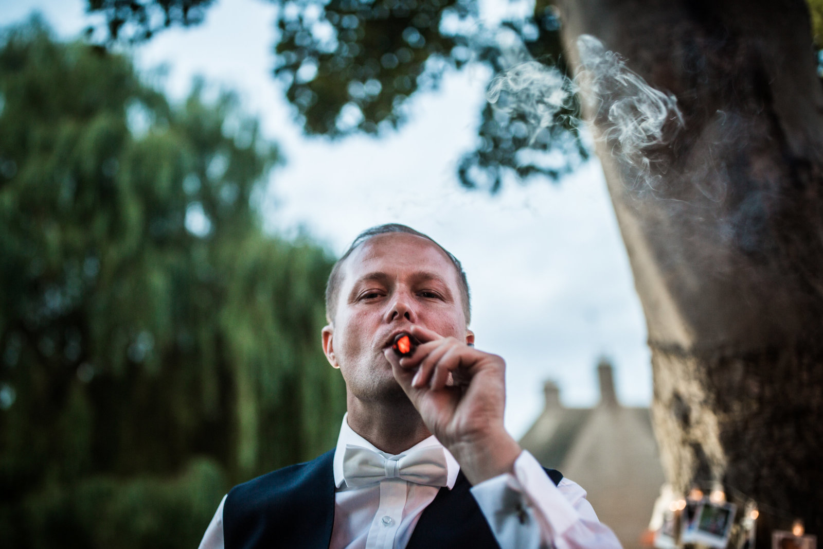A groom looks down at the camera as he takes a drag from a cigar. Smoke is in front of his face and he is stood next to a tree in Norfolk.