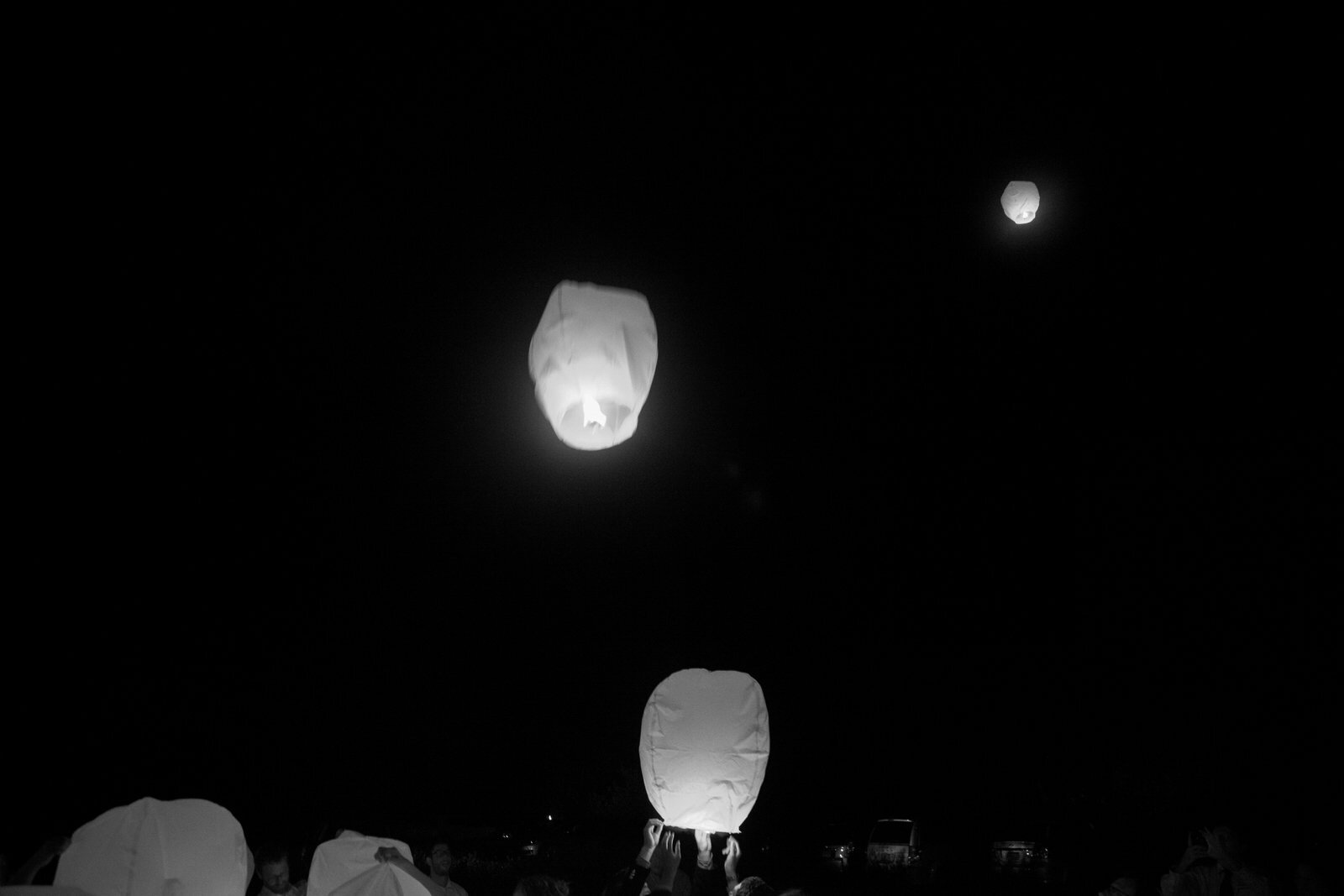 Black and white image of people letting go fire lanterns