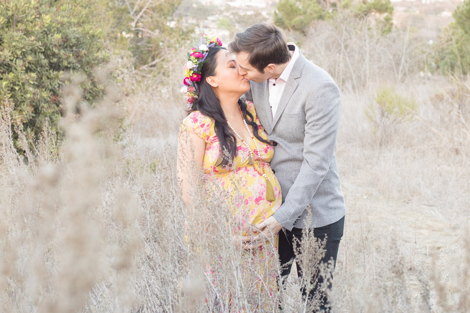 Andrea and Ryan kissing in the middle of the field during their maternity session at Kenneth  Hahn State Park