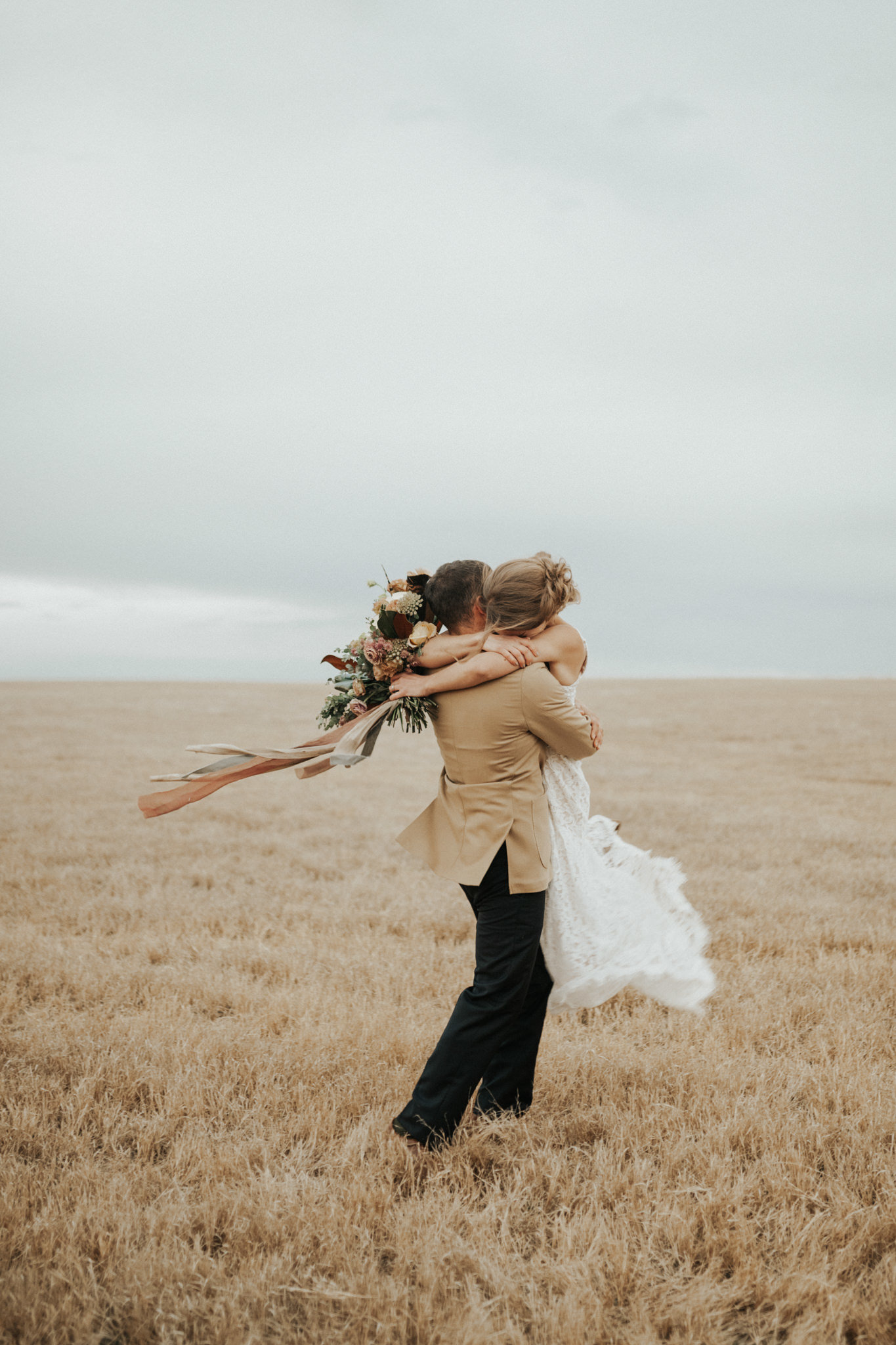A bride and groom photo in an open field at sunset.
