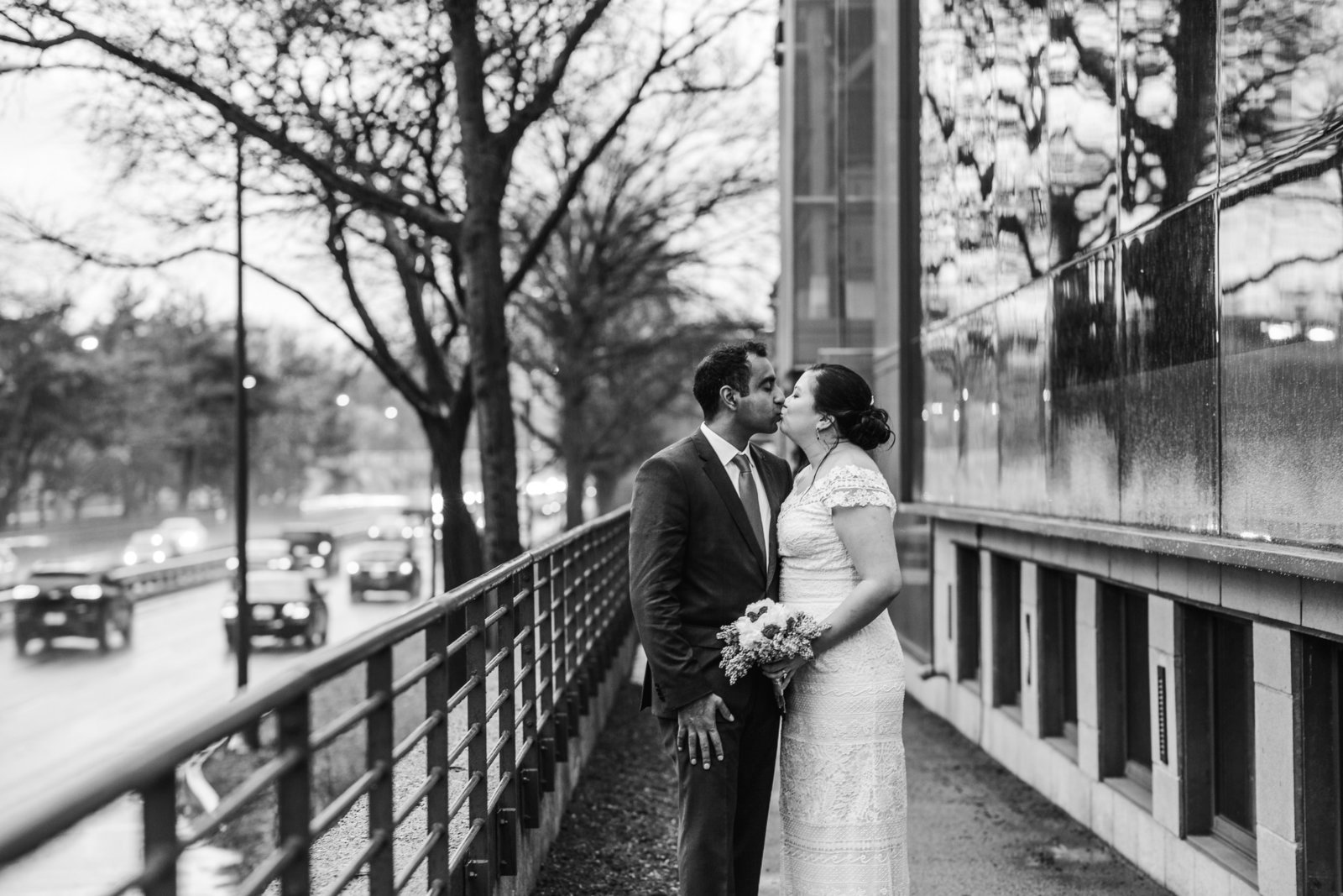 bride and groom kiss next to building in boston