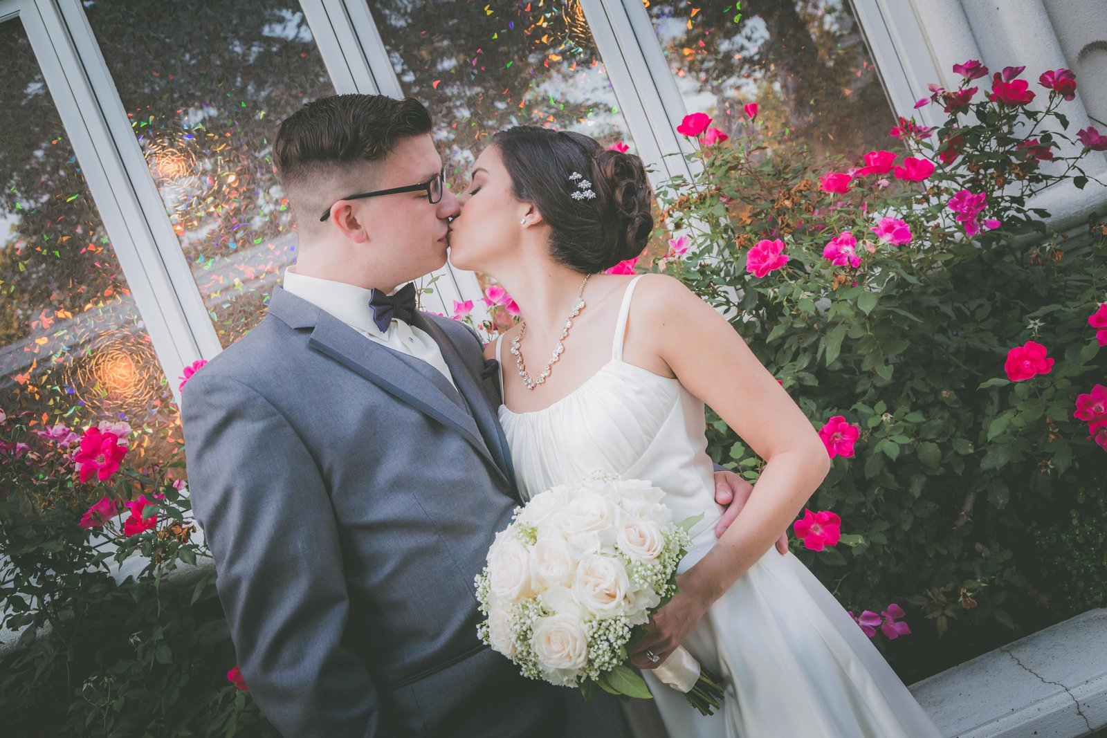 Bride and groom kiss against flower and window background in Connecticut.