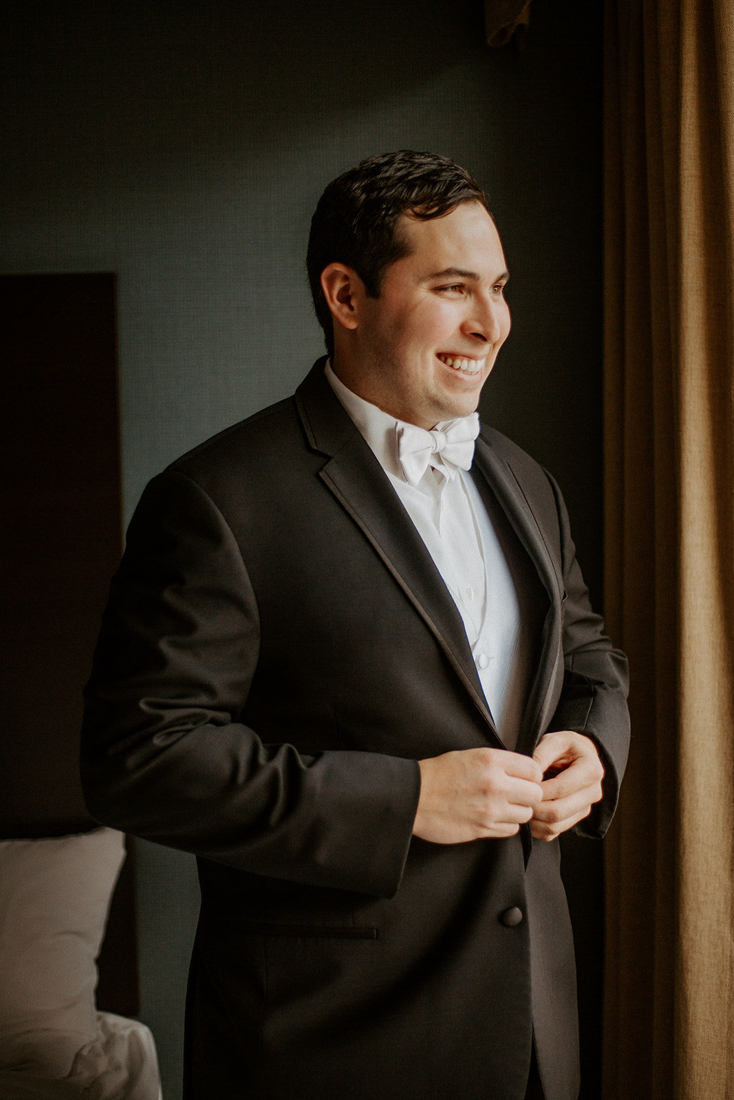 Groom tying his suit coat during his Minneapolis wedding