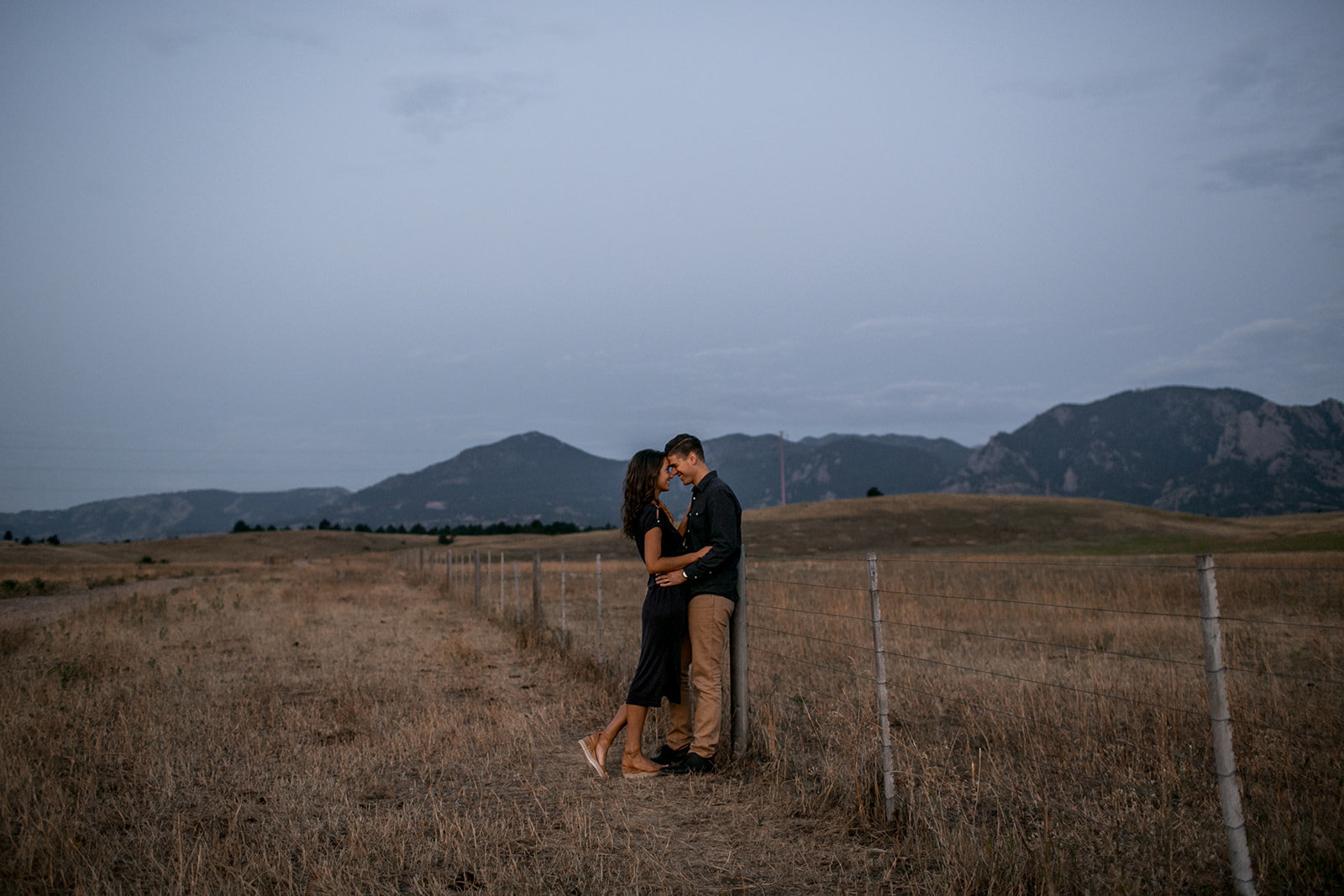 Couple in a field in front of the mountains in Colorado.