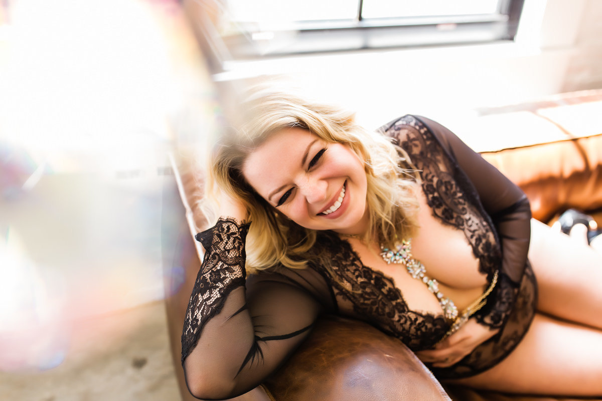 Boudoir photo of a smiling woman laughing on a couch