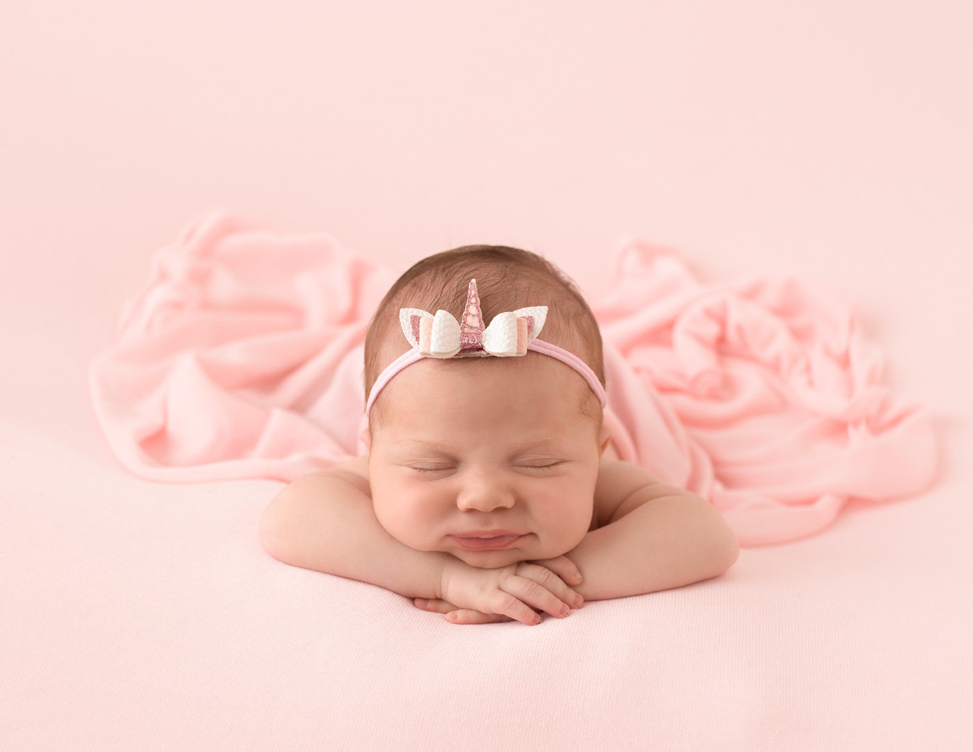 Precious newborn girl posed head on hands in our Rochester NY studio.