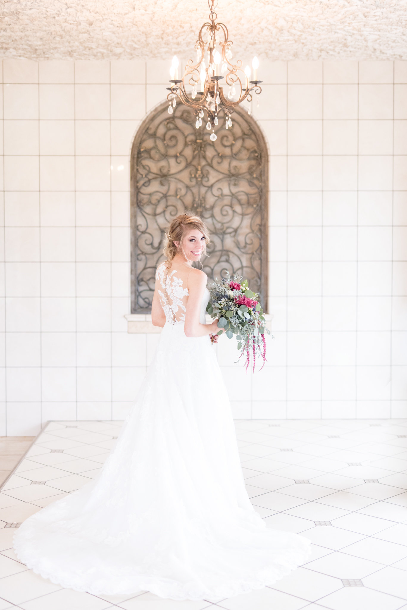 Bride looks at camera under chandelier.